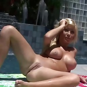 Busty bombshell modeling nude by the pool