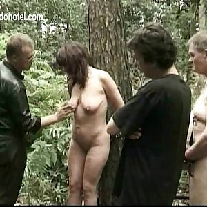Milf slave tied to a tree gets spanked on her gams and hit on her pussy by master