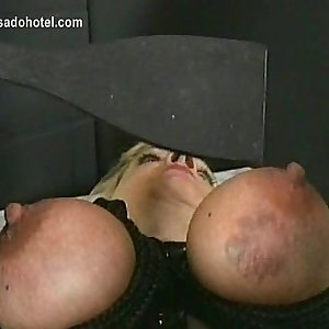 Blond slave with big tits is spanked and got her boobs tied together with a string by master